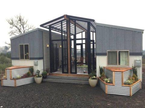 Deux minuscules maisons reliées par une véranda centrale et une terrasse